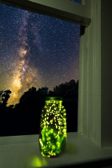 Fireflies In Jar On Window Sill With Night Sky
