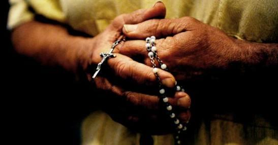 hombre-sostiene-rosario-manos-rezando-entre-dedos