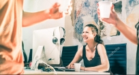 Young business woman having fun working at computer with coworke